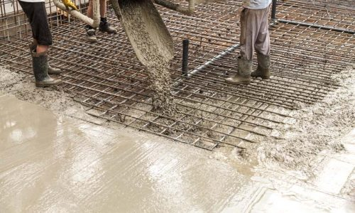 Pouring concrete into the construction of the house. Builders are pouring ready-mixed concrete